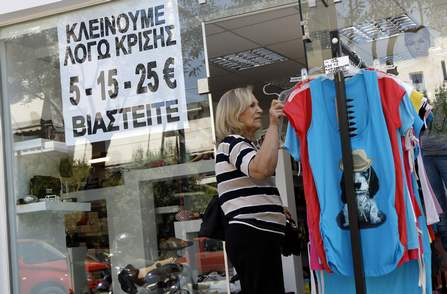 A woman looks at clothing outside a shop where a sign is placed on the window in Athens