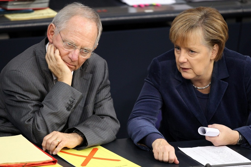 epa02467667 German Chancellor Angela Merkel (R) and German Minister of Finance Wolfgang Schaeuble (L) talk during a debate of the German Bundestag on the 2011 federal budget in Berlin, Germany, 26 November 2010.  EPA/WOLFGNAG KUMM