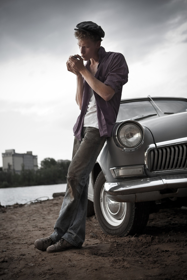 Smoking taxi driver near the vintage car. Retro-styled photo.
