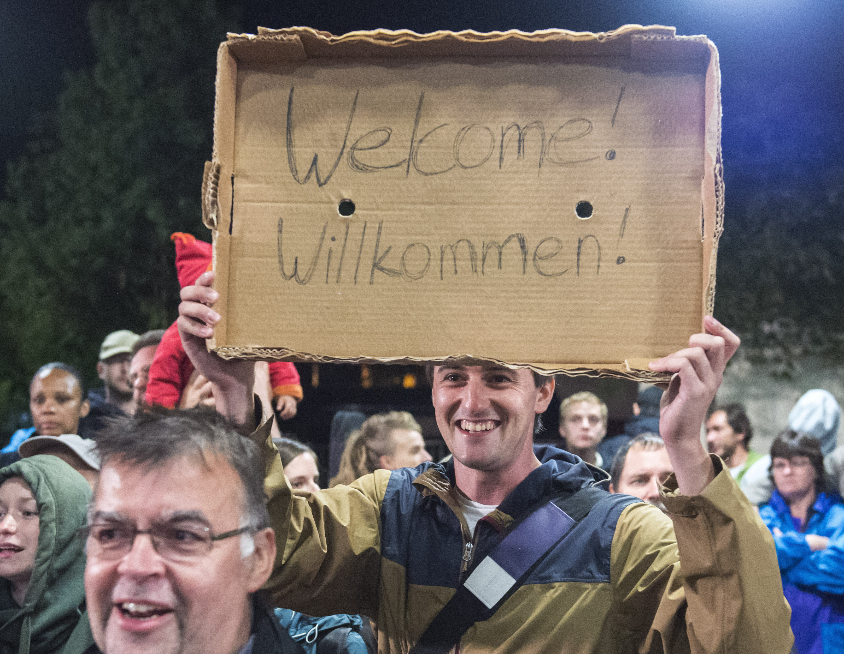 """FILE - In this Saturday, Sept. 5, 2015 file photo, a man holds a """"Welcome"""" sign during the arrival of refugees at the train station in Saalfeld, central Germany. Hundreds of refugees arrived in a train from Munich to be transported by busses to an accomodation center. The United States and the European Union project themselves as models for the world when it comes to democracy and human rights. Yet a common issue, migration, is bitterly dividing each of them(AP Photo/Jens Meyer, File)"""